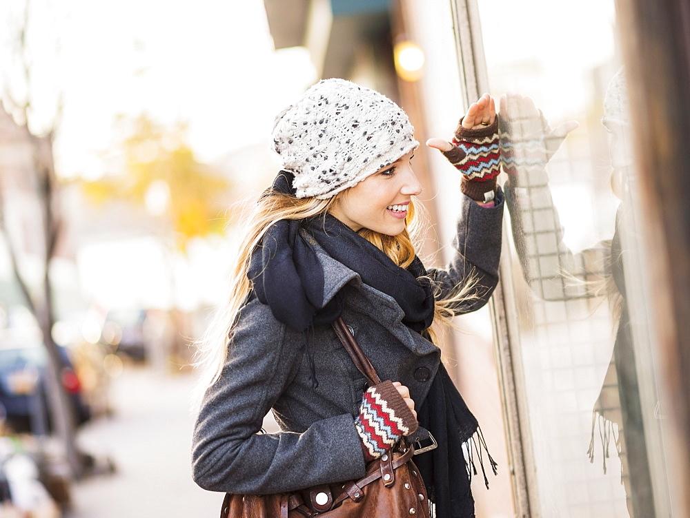 Portrait of blond woman looking at window display, USA, New York City, Brooklyn, Williamsburg