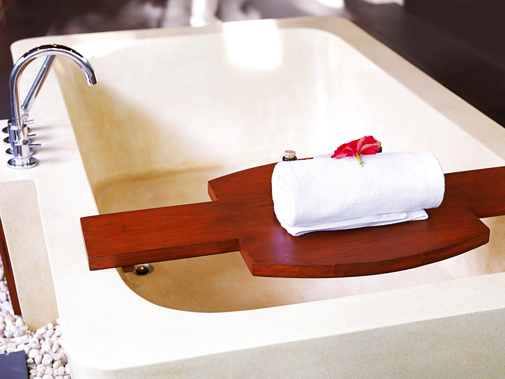 Bathtub with towel on wooden shelf