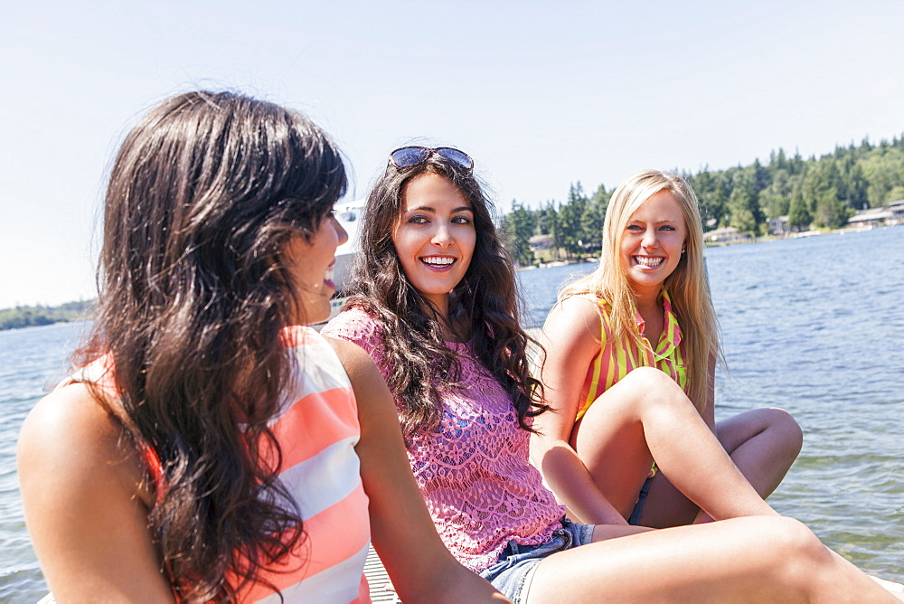 Young women hanging out by lake, USA, Washington, Bellingham