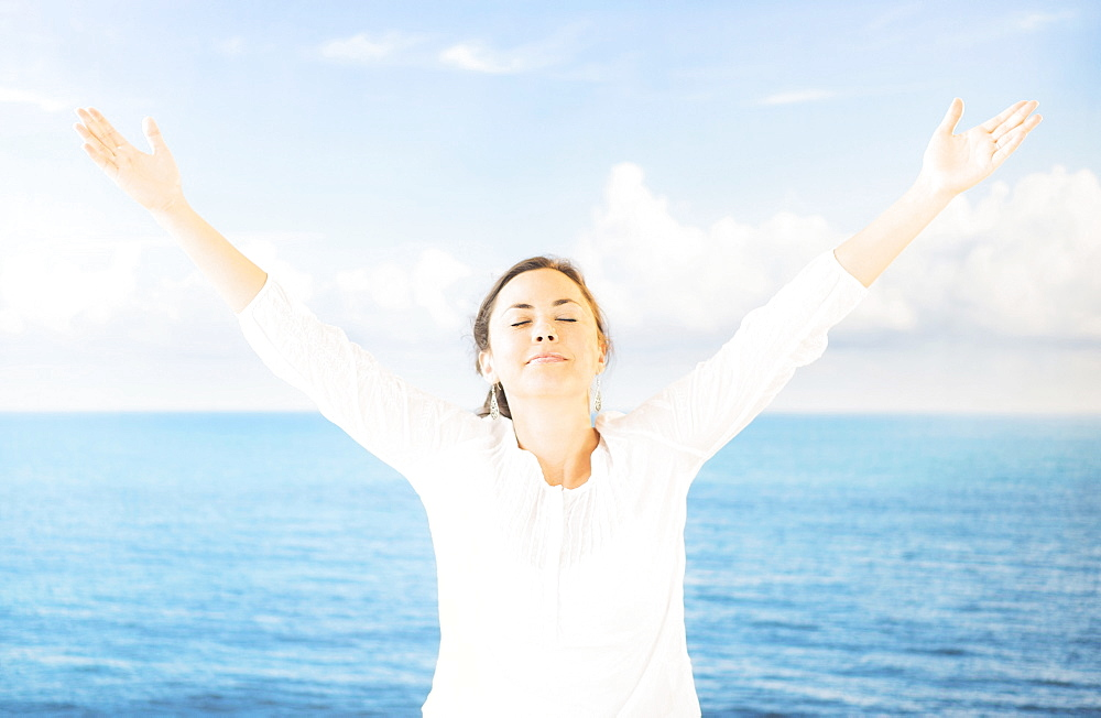Portrait of woman with arms raised in front of backdrop with sea and sky