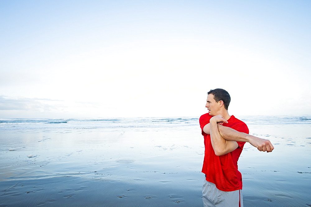 Young adult man stretching on beach, Rockaway Beach, Oregon