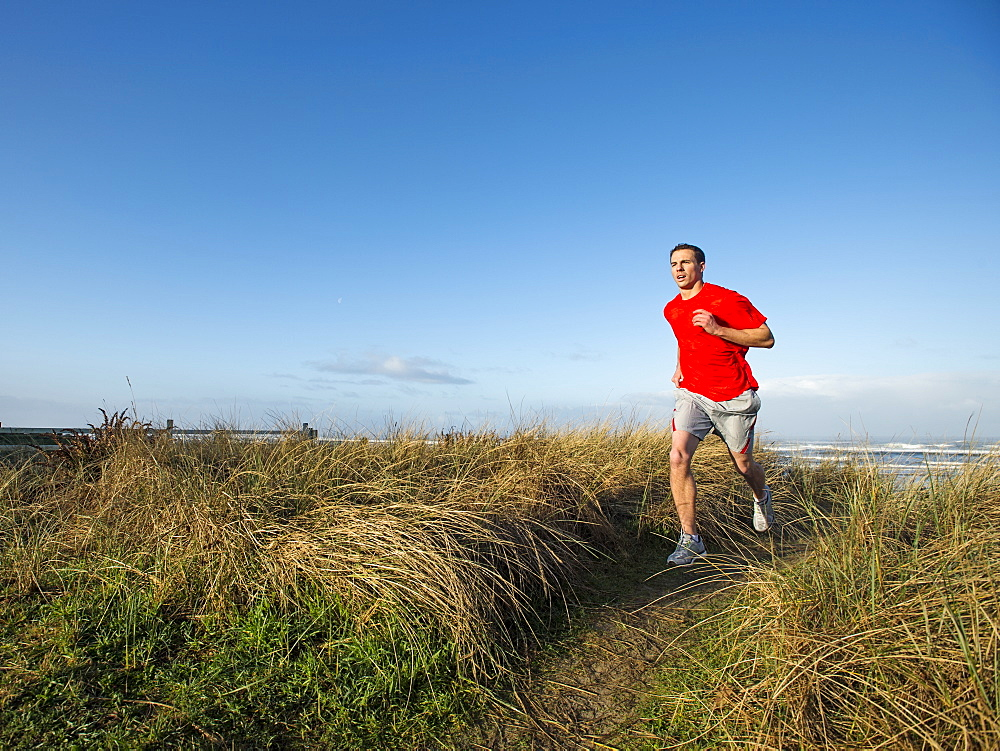 Young adult man running on dune, Rockaway Beach, Oregon