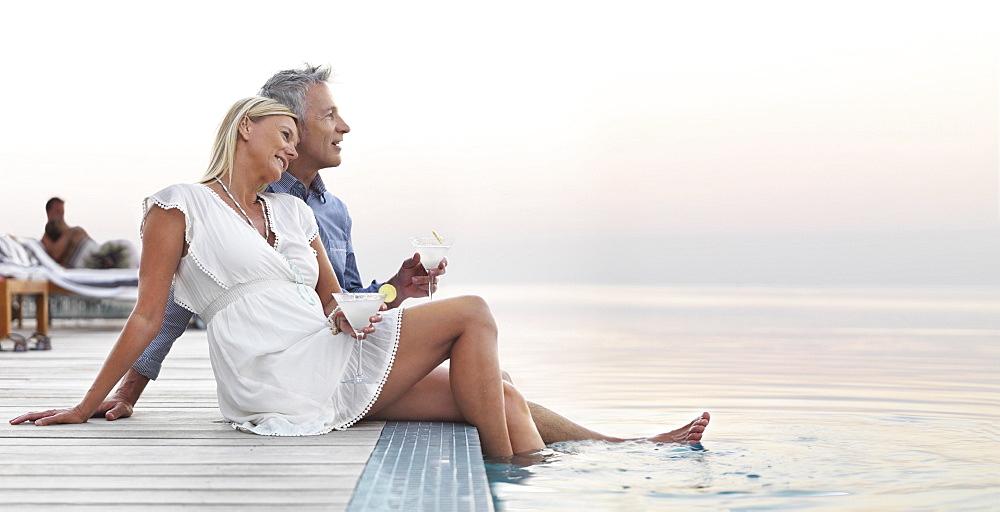 Mature couple sitting by seashore