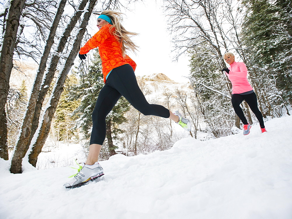 Two women jogging in winter forest, Salt Lake City, Utah USA