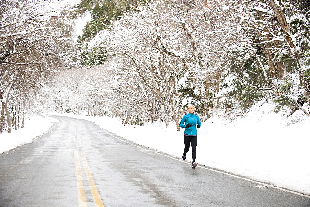 Woman jogging in winter, Salt Lake City, Utah USA