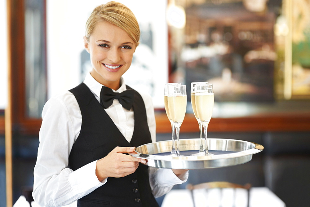 Portrait of waitress holding champagne flutes on tray - 1178-4099