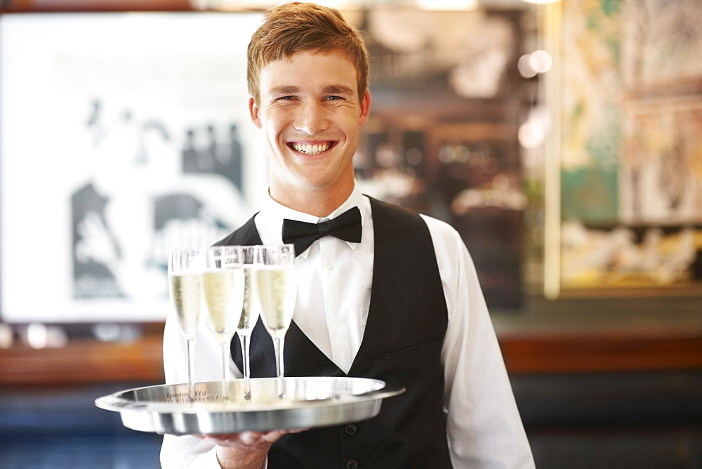 Portrait of waiter holding champagne flutes on tray - 1178-4100