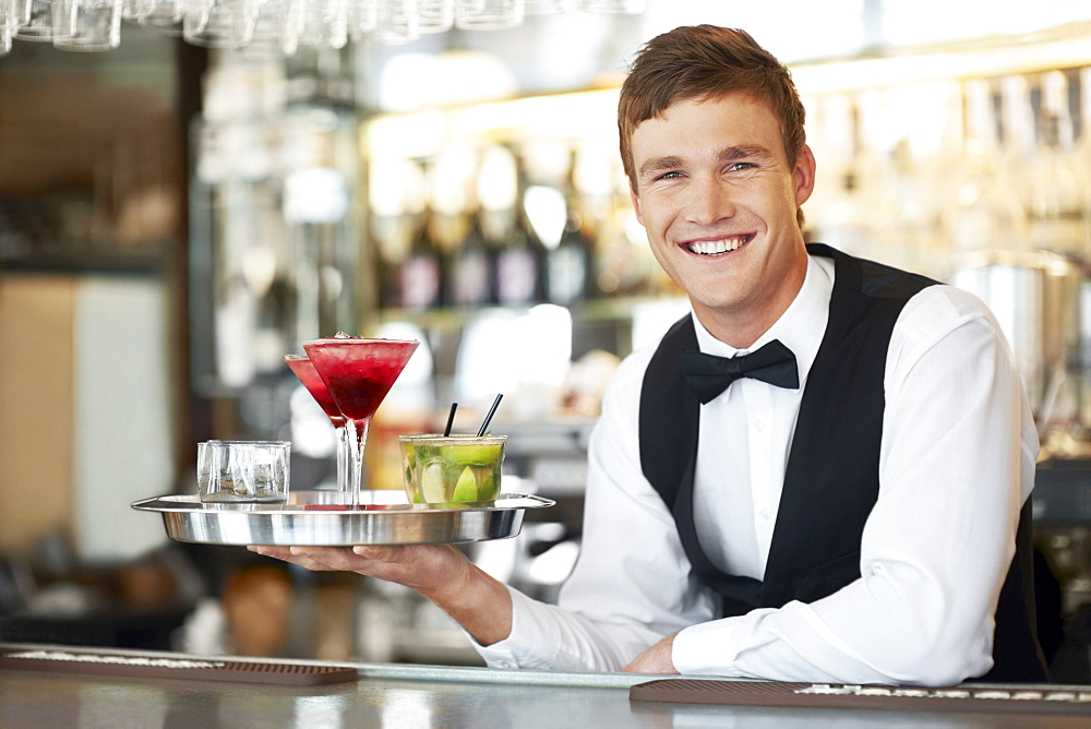 Bartender holding tray with cocktails