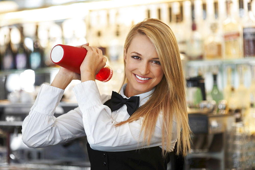 Young female bartender using cocktail shaker
