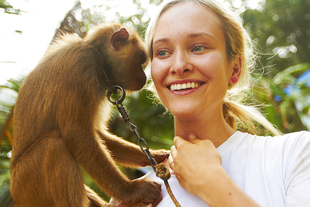 Portrait of young woman holding macaque monkey, Thailand
