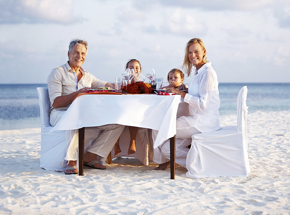 Portrait of parents with daughters (8-9), (4-5) sitting at table on beach, Thailand