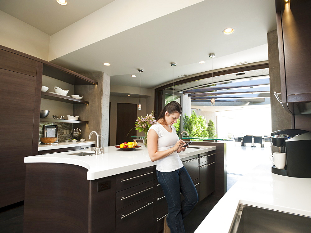 Young woman text-messaging in her kitchen