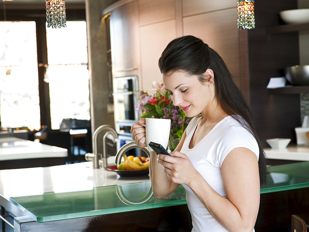 Young attractive woman enjoying morning cup of coffee while checking messages on her mobile phone