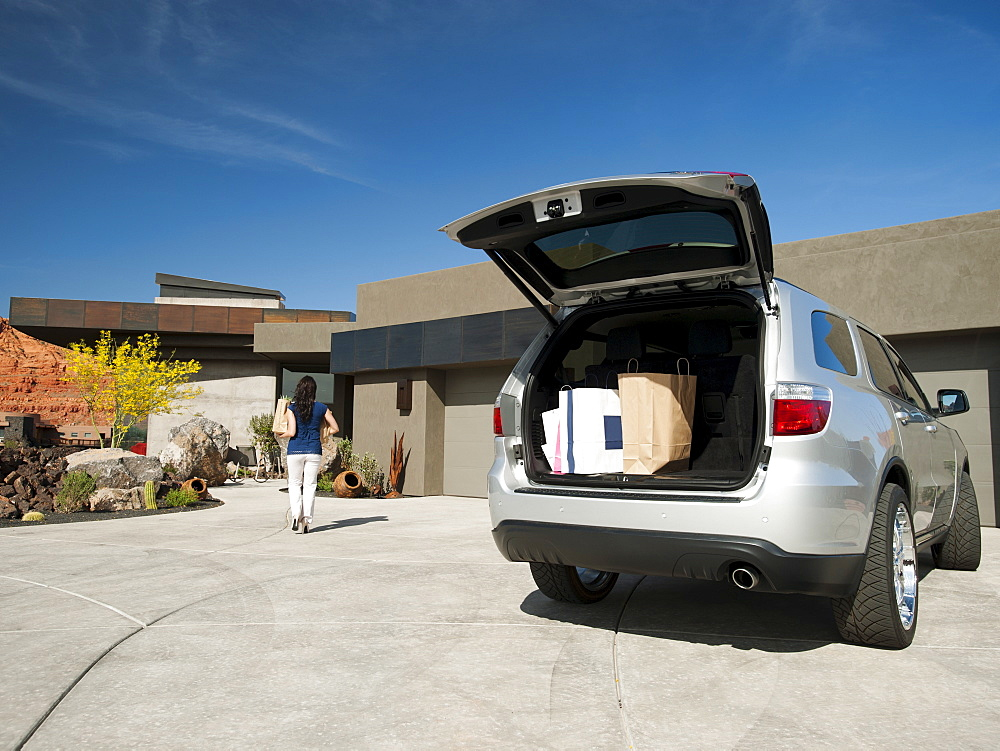 Young woman unpacking shopping from car parked in yard, USA, Utah, St. George