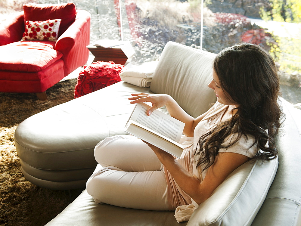 Young woman reading book while sitting on sofa