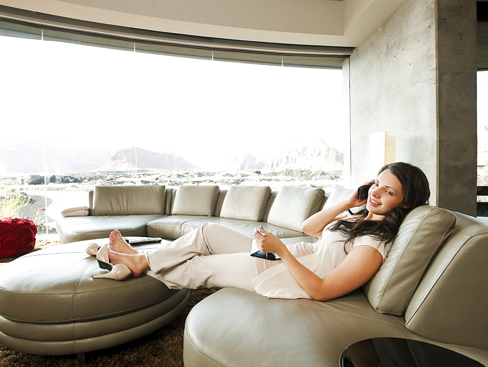 Young attractive woman using mobile phone while sitting in her living room, USA, Utah, St. George