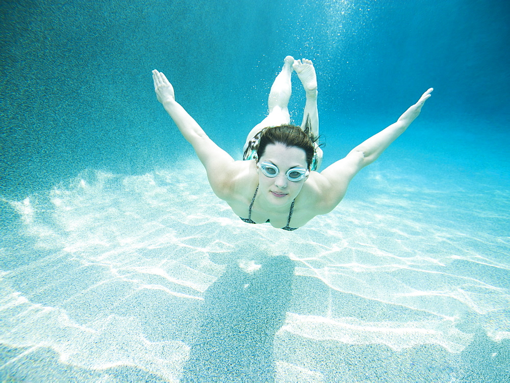 Young attractive woman diving in swimming pool