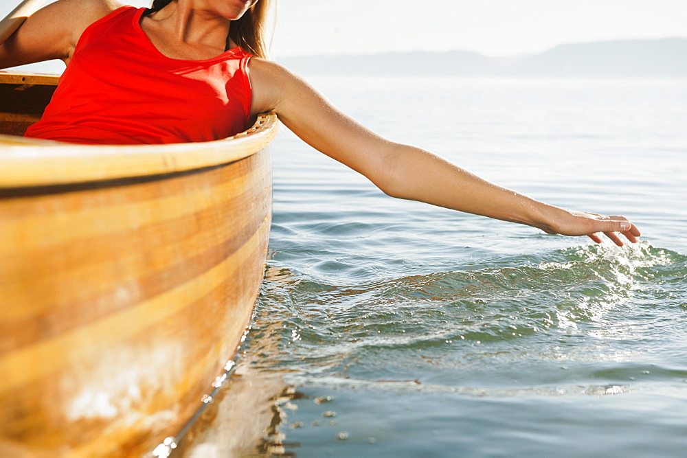 Young woman's hand splashing lake water