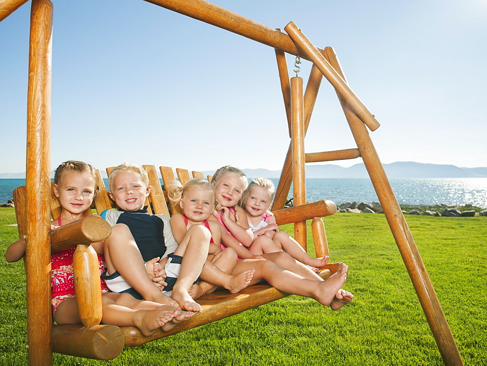 Portrait of children (2-3, 4-5) on swing, USA, Utah, Garden City
