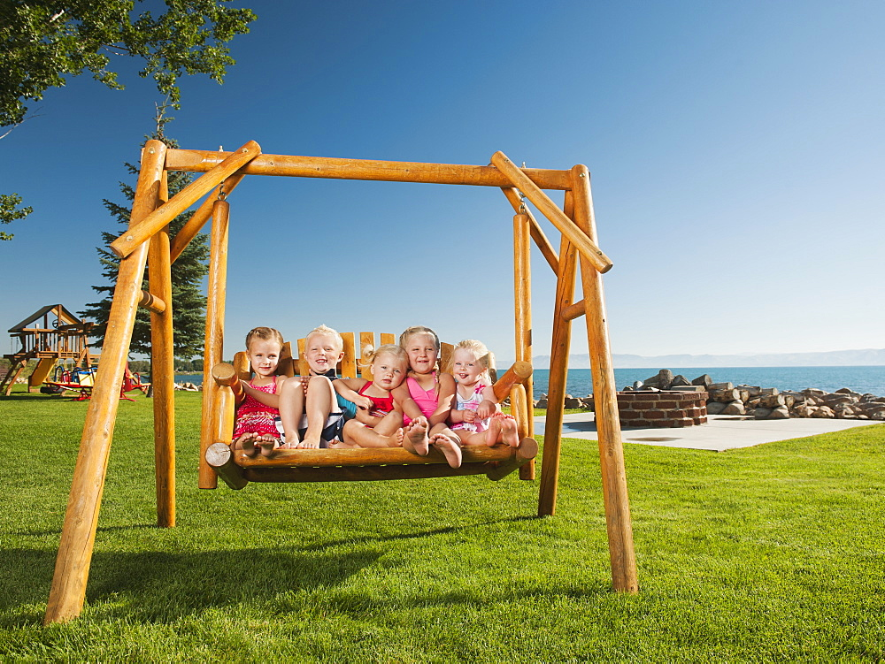 Portrait of children (2-3, 4-5) swinging, USA, Utah, Garden City