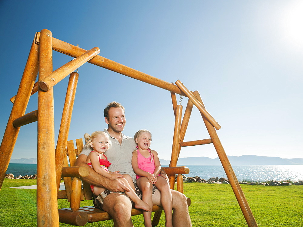 Father with daughters (2-3, 4-5) on swing, USA, Utah, Garden City