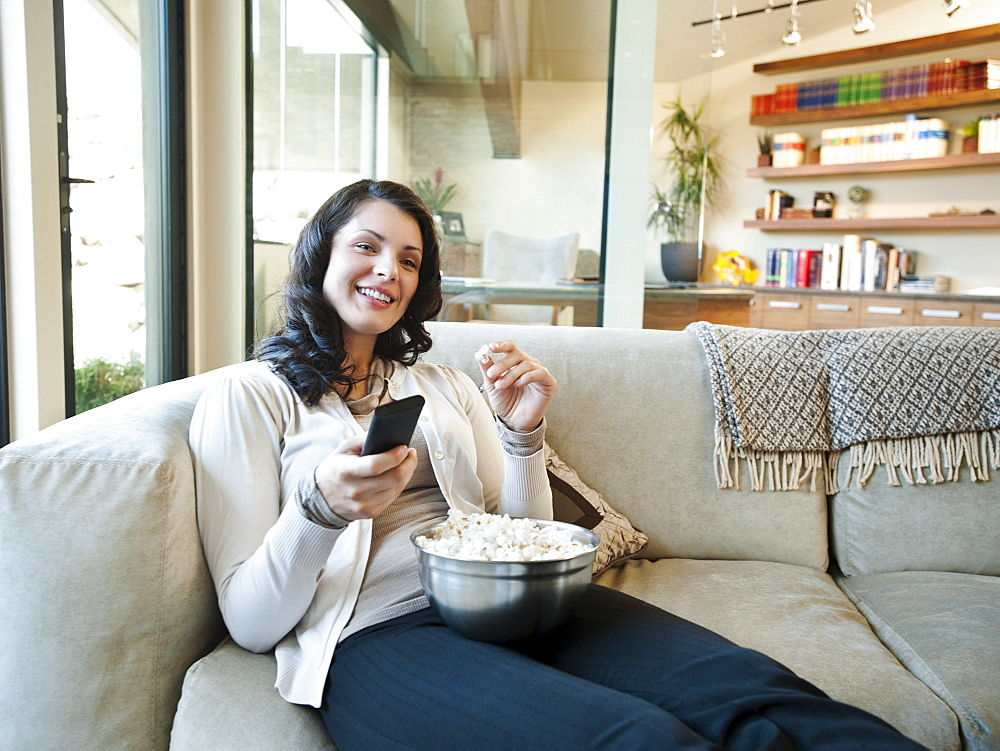 Woman sitting on couch with bowl of popcorn, USA, Utah, St George