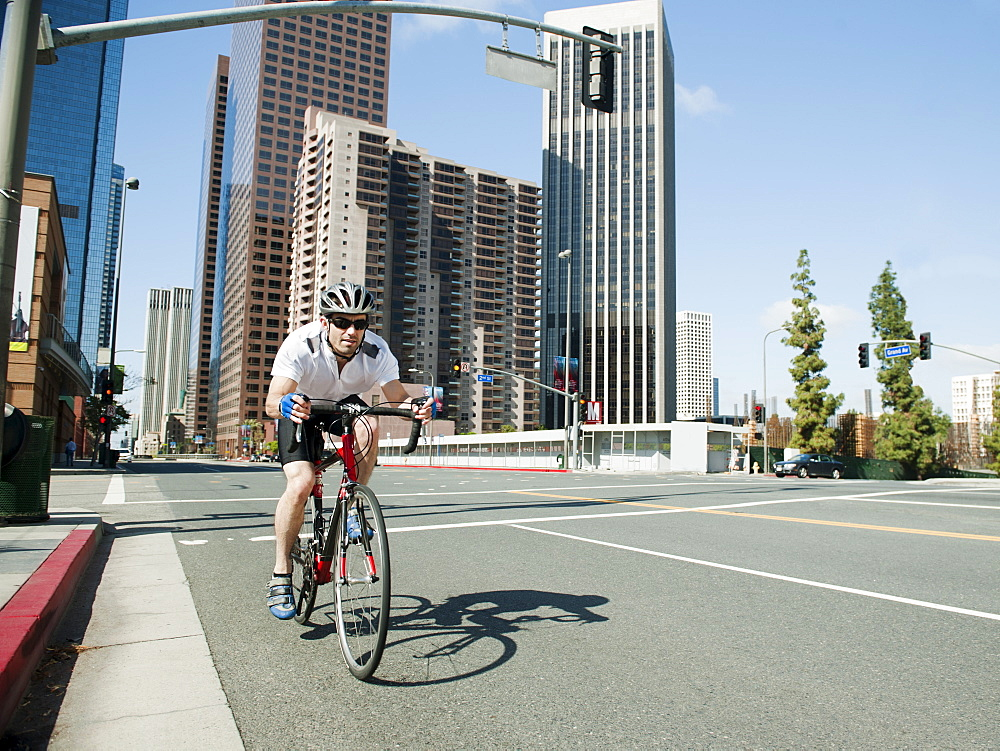 USA, California, Los Angeles, Young man road cycling on city street, USA, California, Los Angeles