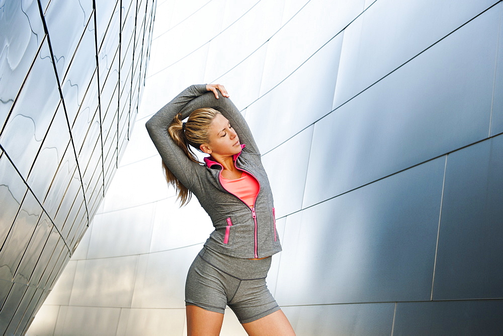 USA, California, Los Angeles, Young woman stretching near modern building, USA, California, Los Angeles