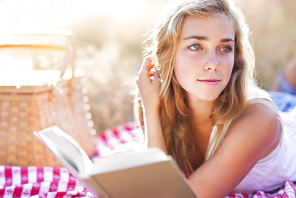 Teenage girl (16-17) taking break from reading book outdoors
