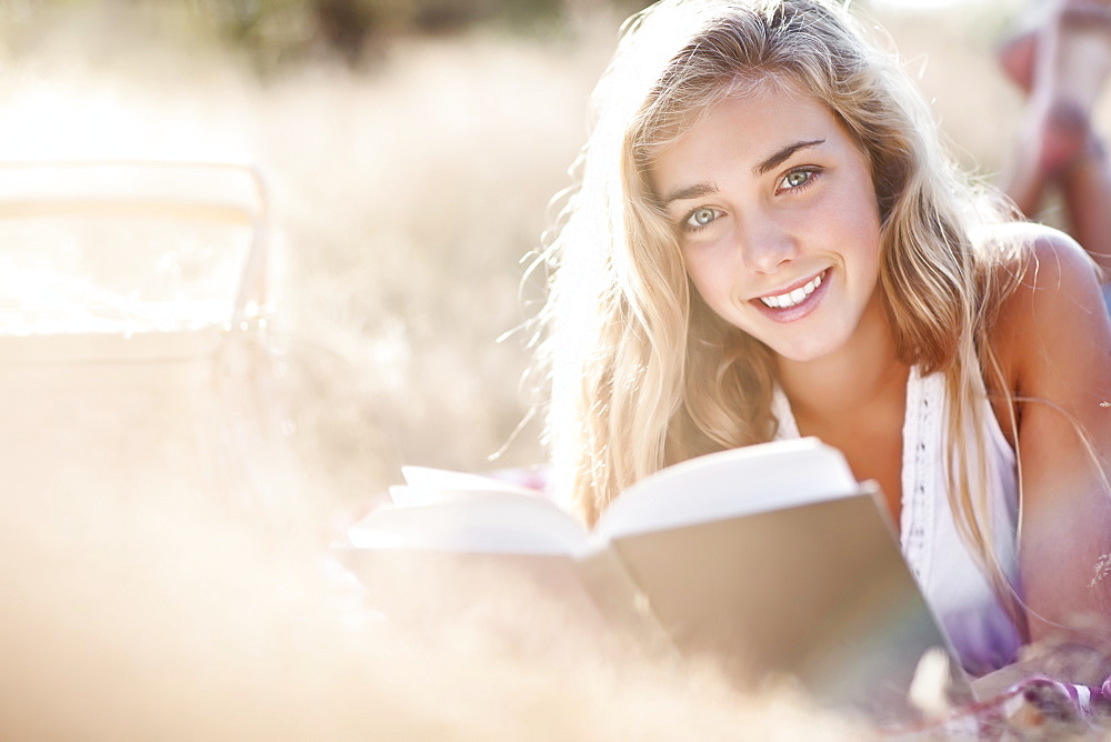 Teenage girl (16-17) posing for portrait while reading book outdoors