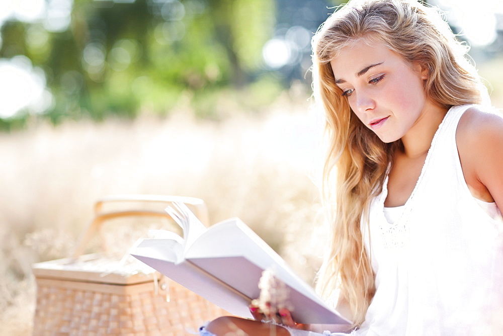 Teenage girl (16-17) reading book outdoors