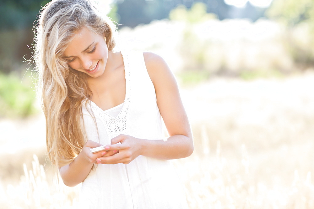 Teenage girl (16-17) text messaging outdoors