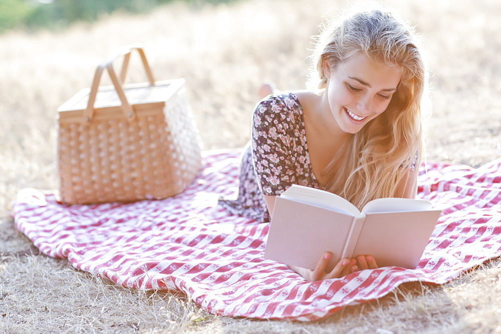 Happy teenage girl (16-17) reading book outdoors