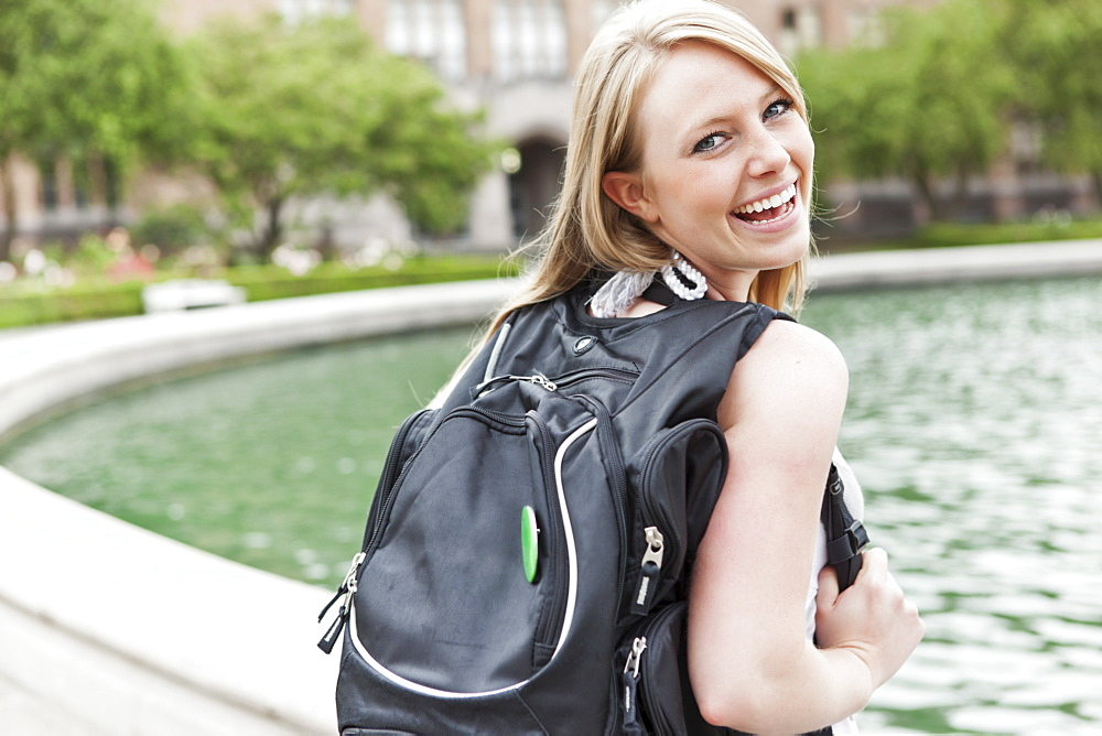 Portrait of female college student showing backpack