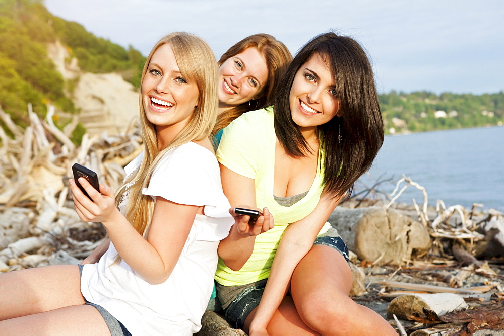 Three young women hanging out on beach, using cell phones