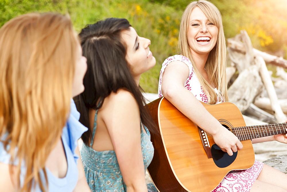 Young women playing guitar on beach