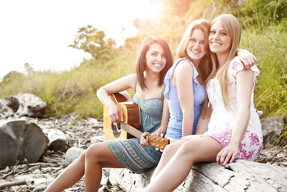 Portrait of young women with guitar on beach
