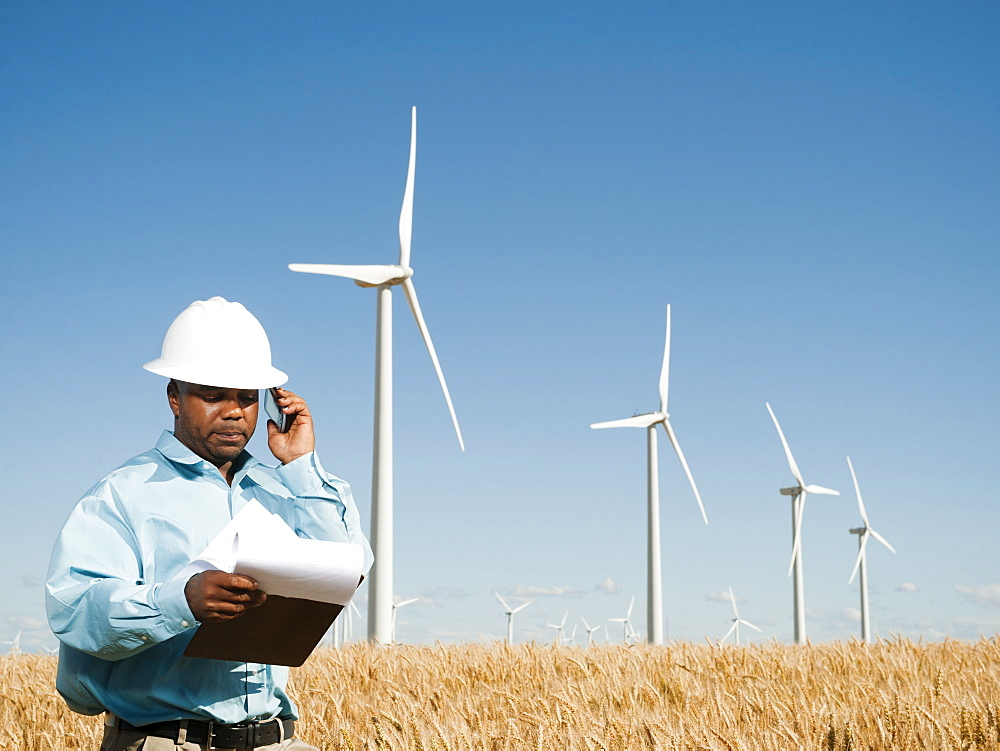 USA, Oregon, Wasco, Engineer standing in wheat field in front of wind turbines