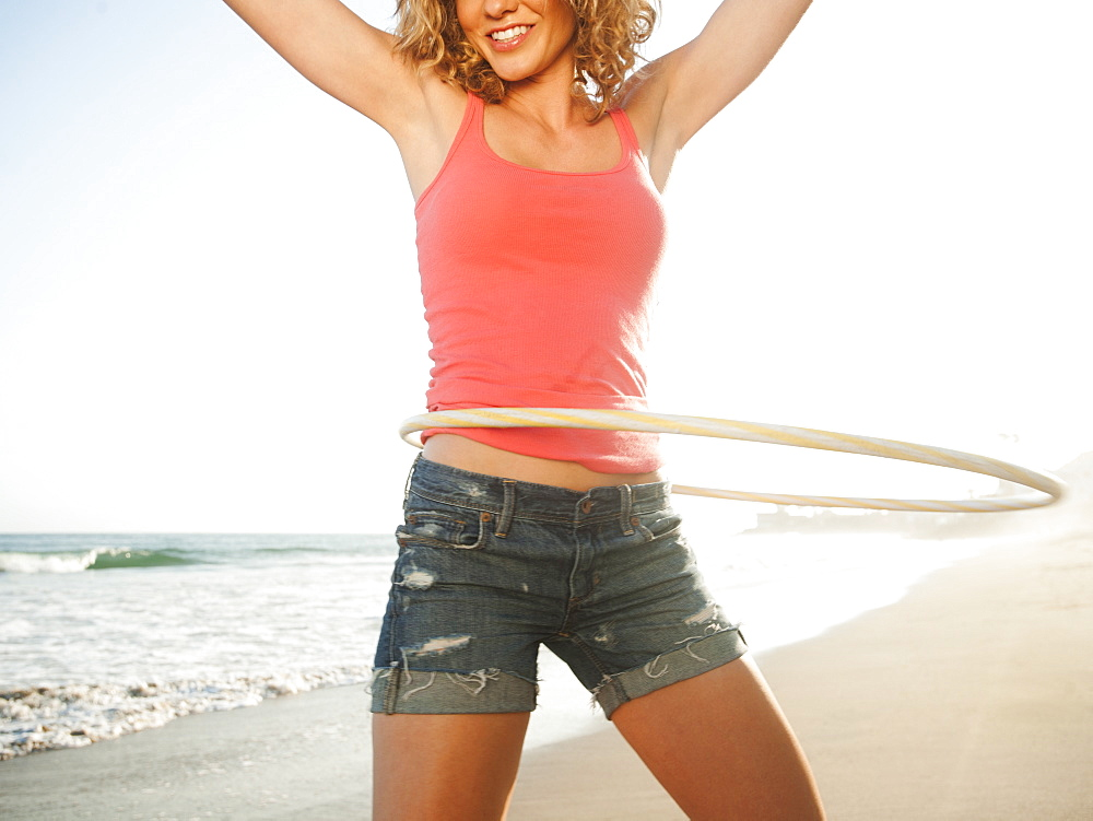 Young attractive woman exercising with hoola hoop