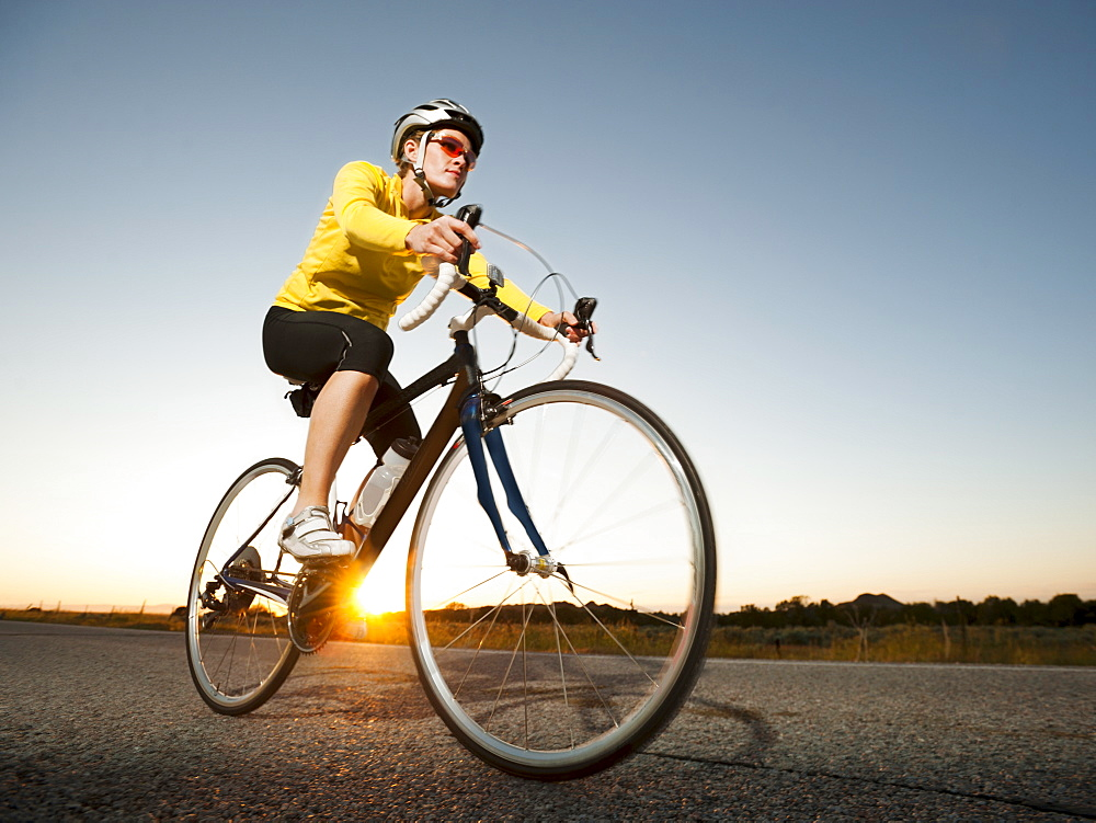 Mid adult woman cycling on empty road