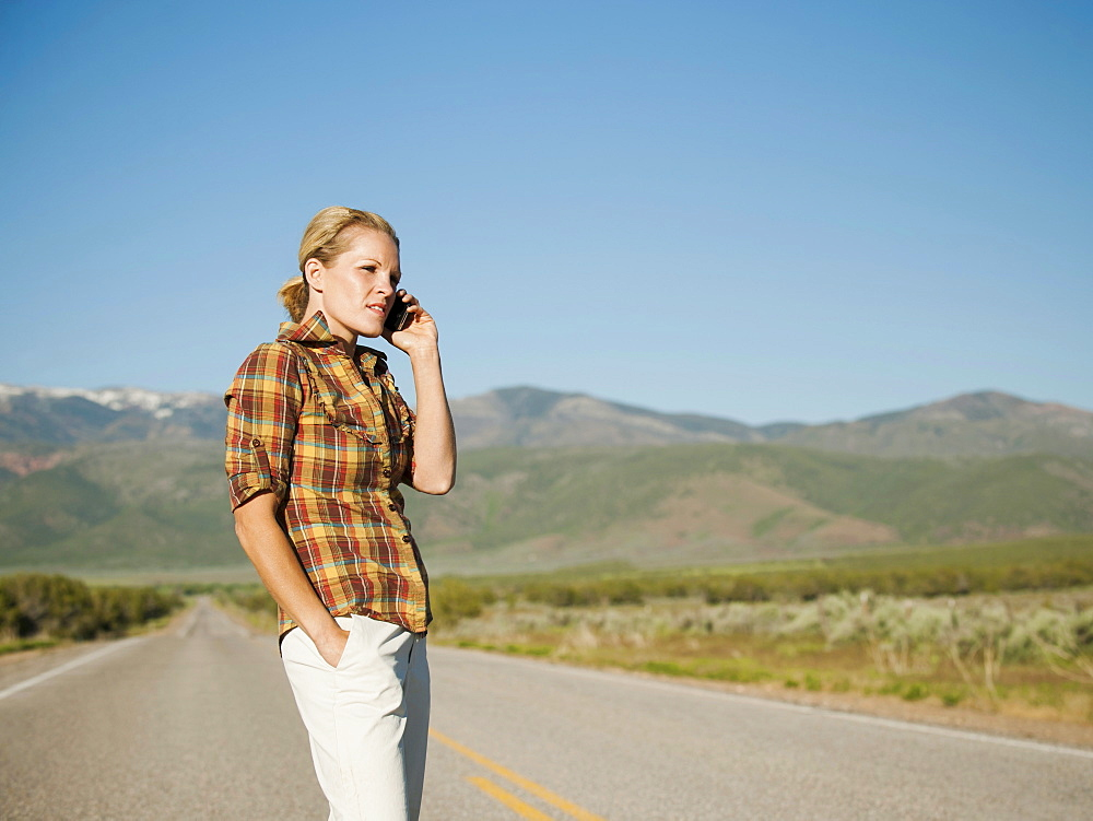 USA, Utah, Kanosh, Mid adult woman calling emergency services on empty desert road