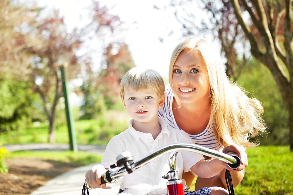 Mother and son (2-3) riding tricycle in park