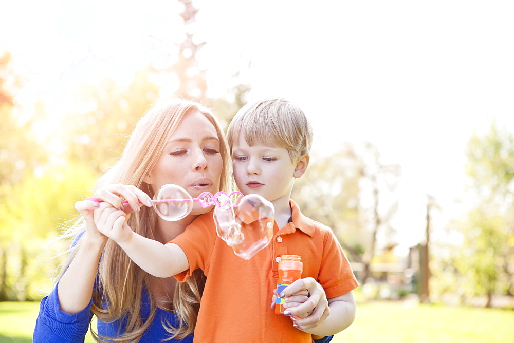 Mother and son (2-3) blowing bubbles in park