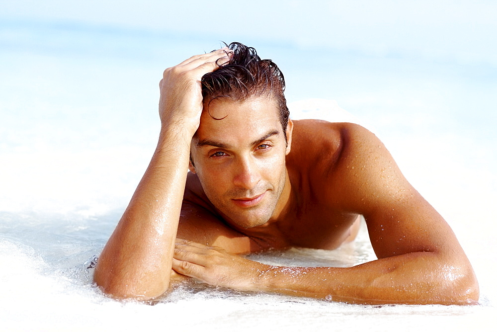 Portrait of attractive young man relaxing on beach