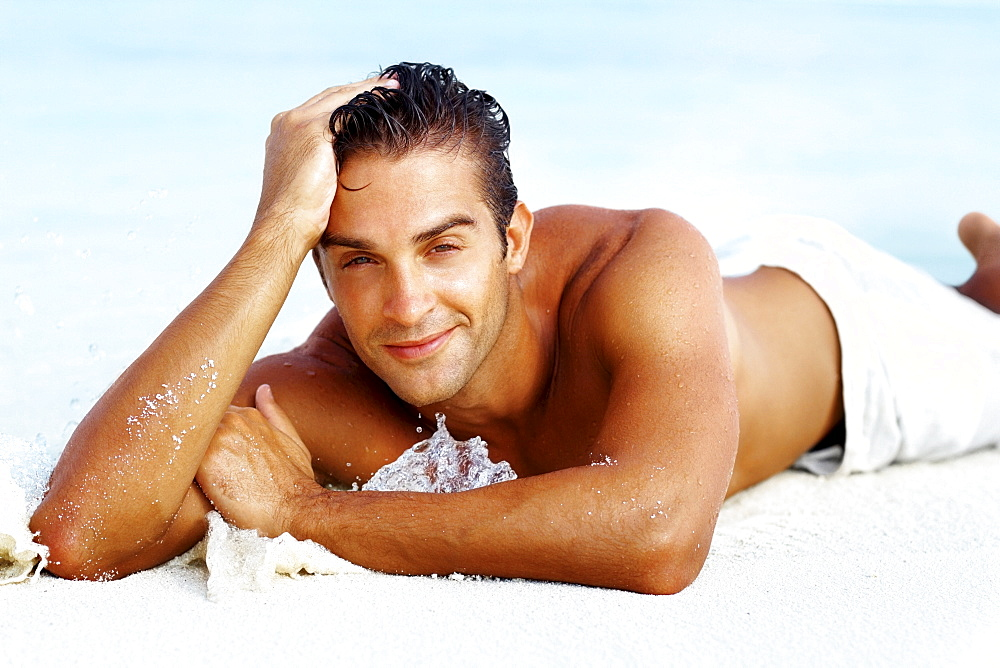 Smart young man relaxing on beach