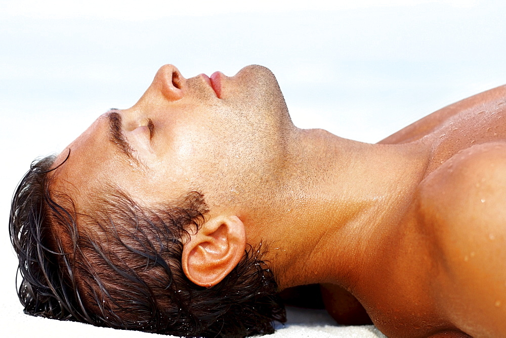 Profile of young guy lying on the beach