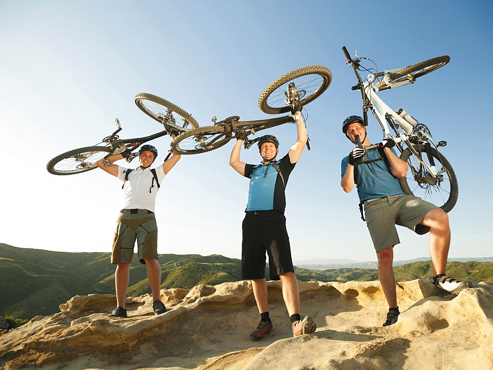 USA, California, Laguna Beach, Mountain bikers on top of hill holding up their bikes
