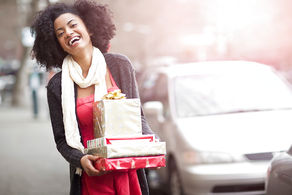 USA, Washington State, Seattle, Young cheerful woman carrying stack of boxed gifts