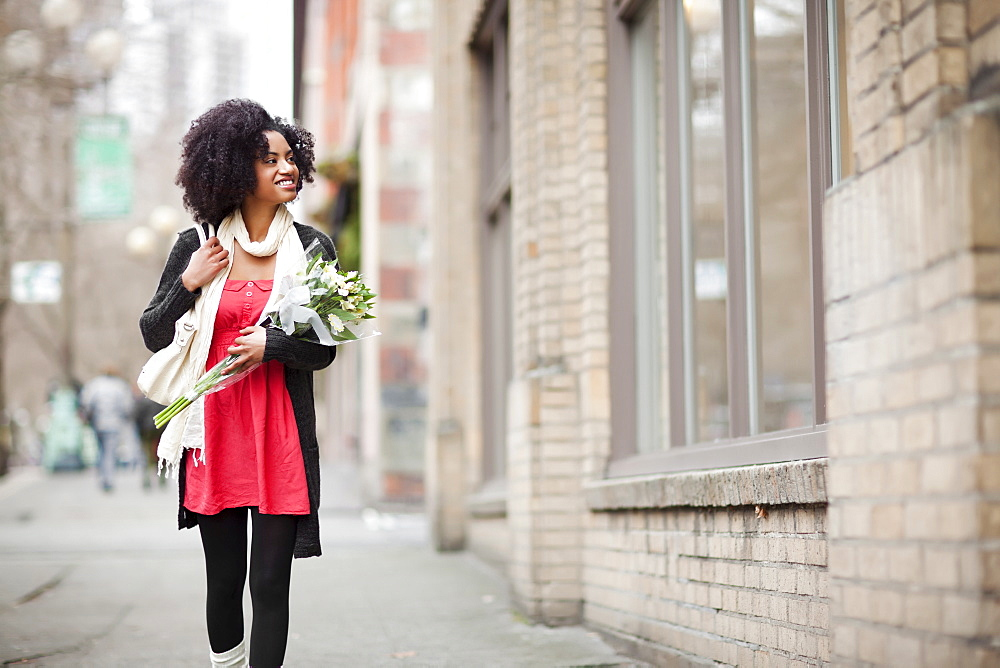 USA, Washington State, Seattle, Young woman walking in street carrying bunch of tulips