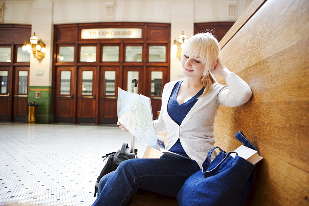 USA, Seattle, Young woman sitting at train station and reading map